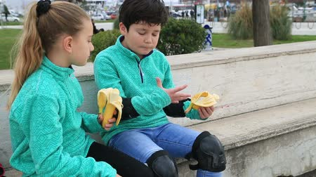 muz : Portrait of a cute young boy and girl with same clothes sitting on a park and eating banana