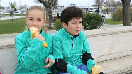 banany : Portrait of a cute young boy and girl with same clothes sitting on a park and eating banana, and smiling to a camera