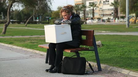 bezrobocie : A fired businesswoman in a suit with a box of personal items sitting on the park bench
