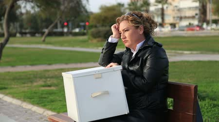 sacked : Fired, sad businesswoman  with box of stuff sitting on the park bench Stock Footage