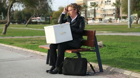 ül : Fired, sad business woman holding box of her things, sitting on the park bench Stock mozgókép