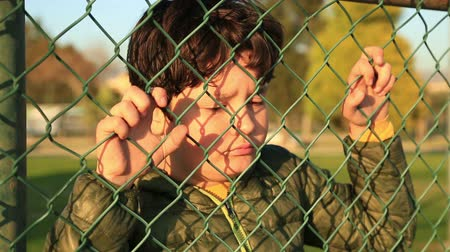 hostility : Portrait of a angry, unhappy, miserable  little boy  behind and clinging to fence
