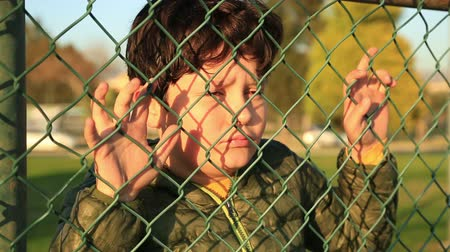 крик : Lonely unhappy, miserable  young boy behind and clinging to fence