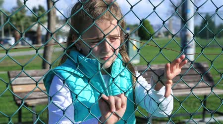 hostility : Portrait of a angry, unhappy, miserable  little girl  behind and clinging to fence Stock Footage
