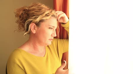 depressão : Portrait of a unhappy, middle aged woman looking out the window Stock Footage