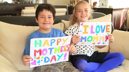 dát : Happy cute little girl and boy smiling to a camera and showing personal notes for mothers day Dostupné videozáznamy