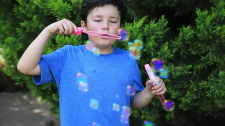 raios de sol : Portrait of a cute little boy is blowing a soap bubbles