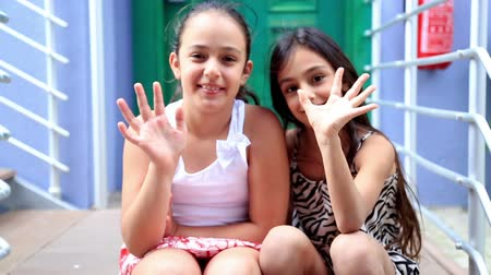 сестра : Portrait of a smiling, cute girls sitting in front of the door and waving hand to camera