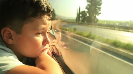 одиноко : Portrait of a sad young boy looking out bus window outside, while it moving. Стоковые видеозаписи