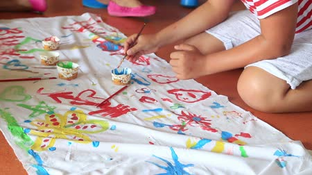 anaokulu : Child painting on a fabric in play room. Child care. Stok Video
