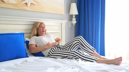 żołądek : Woman having a painful stomach ache Lying on a bed, hands on abdomen Wideo