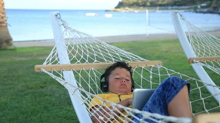 toco : Young boy with earphone using i pad in a hammock Vídeos