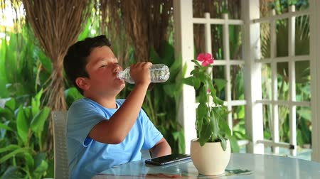 caffe : Portrait of a cute young boy drinking water from a bottle outdoor
