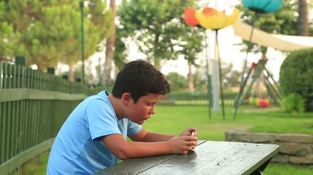 prole : Child relaxing with smartphone in park.