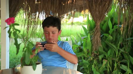 boyish : Young boy gaming on the smartphone.