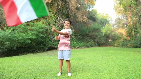 İtalyan : Portrait of a young boy holding and waving the flag of Italy at the park Stok Video