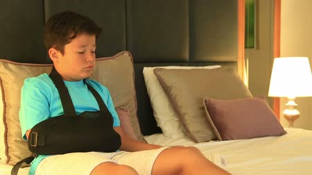 pétala : Portrait of a painful, bored young boy with injured arm watching television in the bedroom