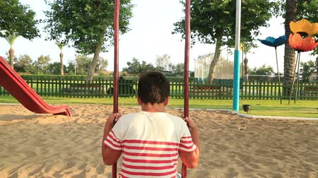 frustração : Portrait of a lonely thoughtful schoolboy on swing at the playground Stock Footage
