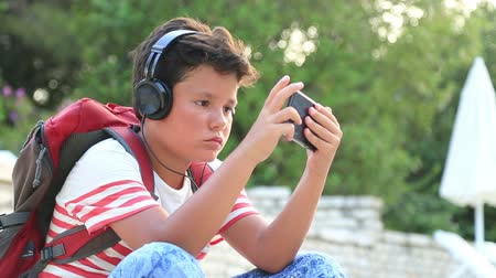 aktywność : Young boy  playing  with mobile smartphone at the outdoor. Smartphone addiction Wideo
