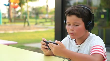 boyish : Young boy with headphone sitting at the park, gaming on the smartphone. Smartphone addiction Stock Footage
