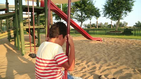 frustração : Lonely, sad preteen boy sitting on the swing at the playground