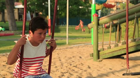 lonely : Lonely, sad schoolboy swinging at the playground Stock Footage