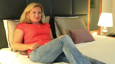 apprehensive : Blond woman lying on a bed and  watching a horror movie in the tv in a bed room Stock Footage