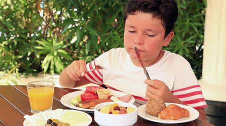 kruvasan : Young boy eating breakfast at the restaurant