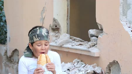 голодный : Portrait of a frightened child eating bread, poverty and hunger concept