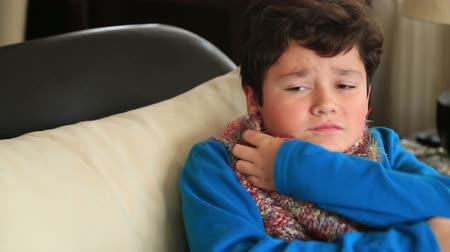 sentimentos : Sick young boy sitting at home feeling ill, has flu, fever, cold and cough