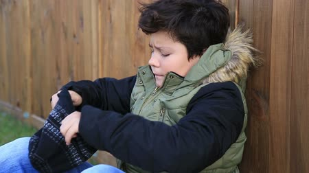 boyish : Handsome young boy sitting  in winter try to warm up his head and hand