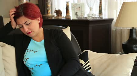 divórcio : Portrait of a sad woman with red hair siting alone at the home Stock Footage