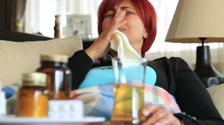 doente : Sick middle age red hair woman is coughing on the couch. She has a flue and fever.