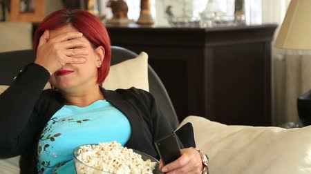 apprehensive : Portrait of a red hair woman sitting on sofa  and  watching a horror movie at home interior Stock Footage