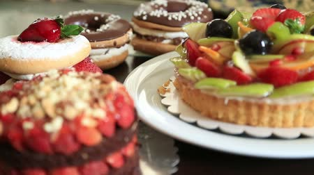 gedroogde vruchten : Assorted fruit tartlets, donuts and pieces of cakes Stockvideo