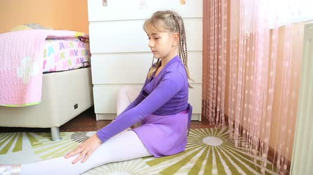 kostüm : Young ballerina girl doing stretching exercises seated on the floor as they warm up before practice