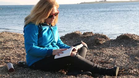improvised : Middle aged woman warmly clothed on the beach in autumn, relax and reading book