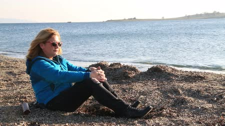 carrancudo : Thoughtful, pensive woman on winter sea beach sitting Stock Footage