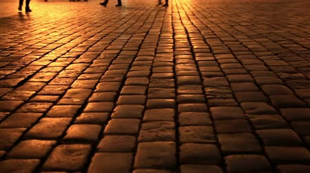 treading : People walking on a cobblestone street  by colourful neon street lights