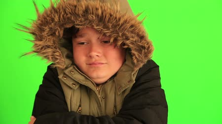 maska : Winter portrait of young boy, kid in winter clothes trying to warm against chroma key green screen background Wideo