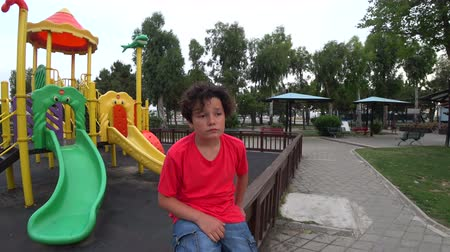 frustração : Portrait of a depressed lonely, sad preteen boy at the playground Stock Footage