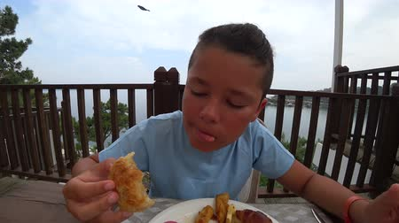 блин : Young boy having breakfast at the outdoor restaurant