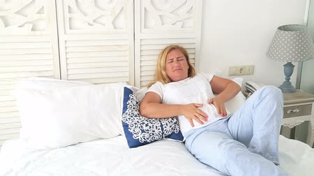 gyomor : Portrait of a woman with blonde hair laying on a bed having strong stomach ache  hands on abdomen Stock mozgókép