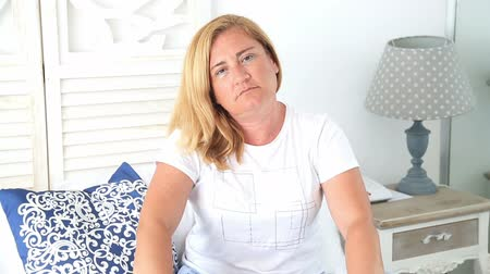 otuzlu yıllar : Sad  woman sitting on bed looking at camera with a serious expression Stok Video