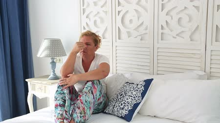 düşünürken : Attractive, middle aged woman having a migraine sitting on a bed at home