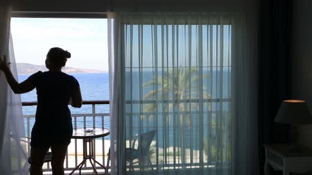 unveil : Woman watching sea view from balcony