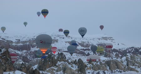 montgolfière : Hot air balloons flying over famous city Cappadocia at winter time Goreme Nev�ehir Turkey 28 Jan 2018 Cappadocia�s �fairy chimneys,� cone-shaped rock formations.