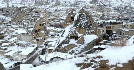 фасонный : A view of ancient village with cave houses on a winter snowly day in Urgup Nevsehir Cappadocia Turkey. 28 Jan 2018 Cappadocia�s �fairy chimneys,� cone-shaped rock formations. Стоковые видеозаписи