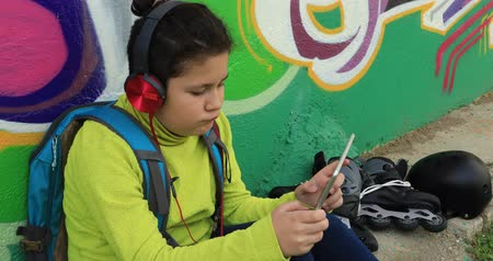 boyish : Young preteen boy with headphone  using digital tablet computer at the outdoor