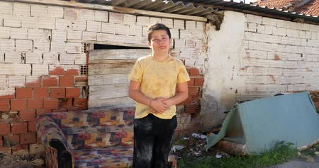 migrants : Portrait of a caucasian poor young boy  infront of the slum and looking sadly Stock Footage
